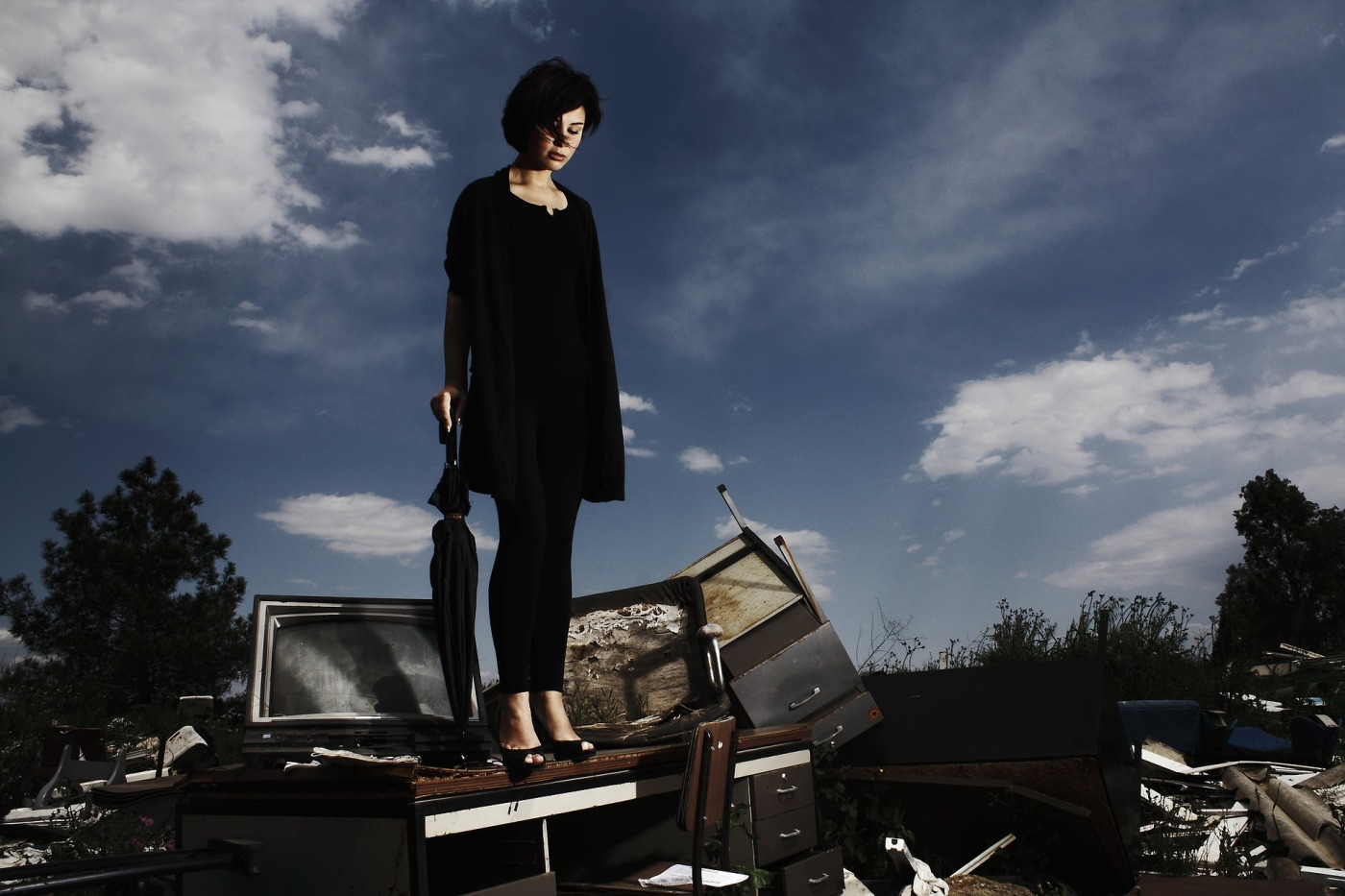 woman on top of discarded junk, holding and umbrella